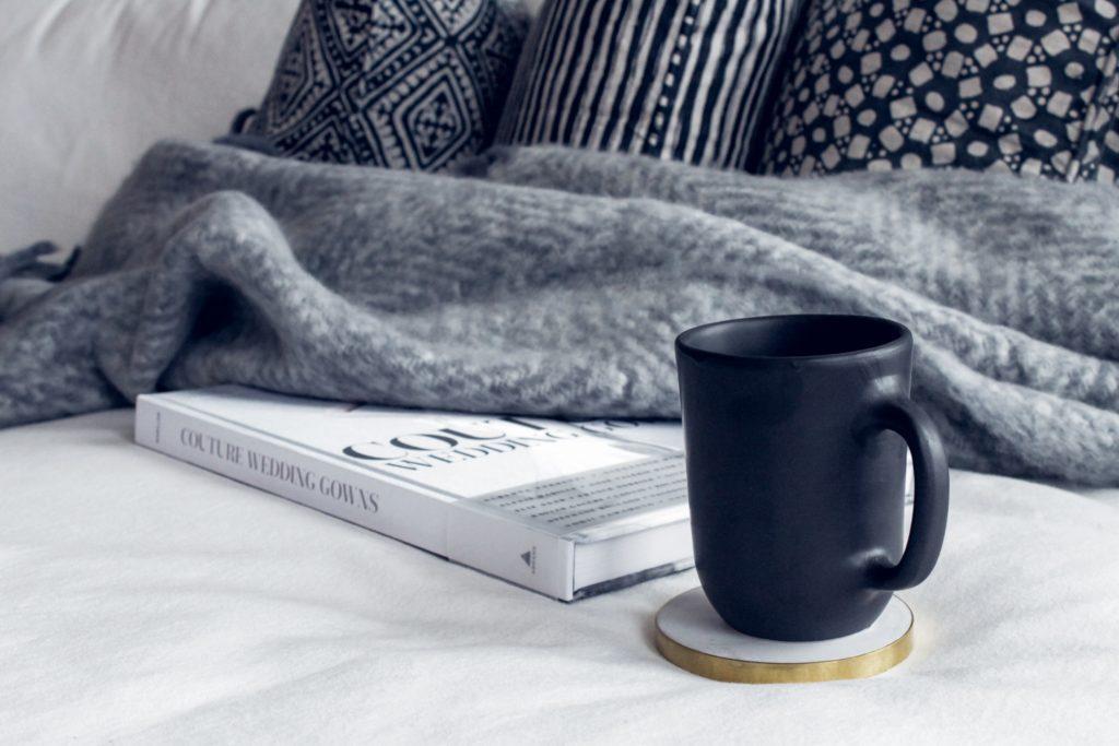 Kuvituskuva, jossa on kahvikuppi ja kirja pöydällä.